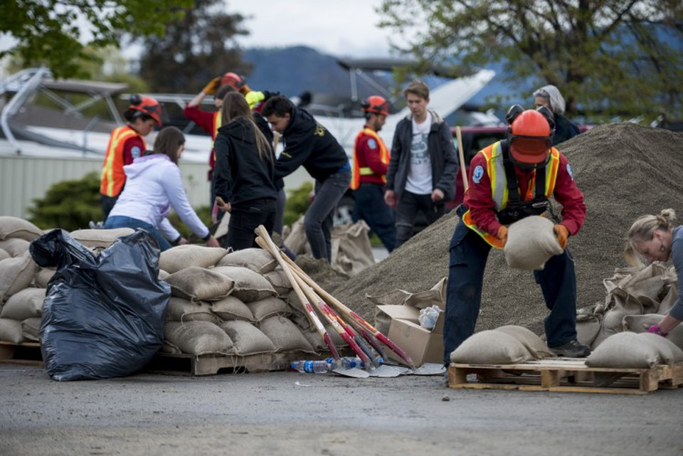 Emergency response workers pile sandbags for critical infrastructure protection.