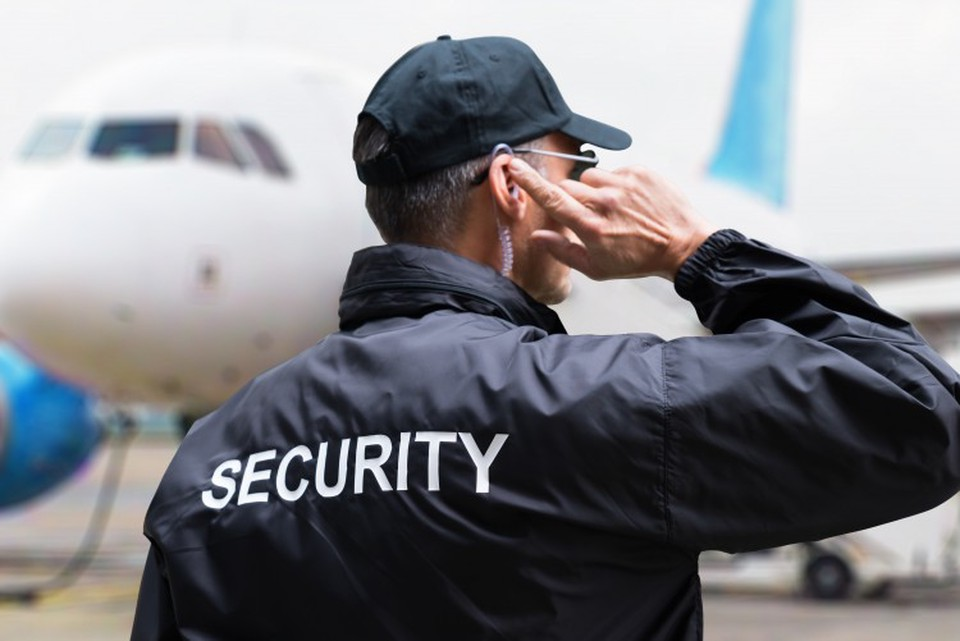 A homeland security agent stands on the tarmac listening to instructions through his earpiece.