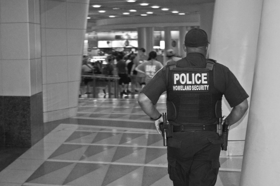 Homeland security officer walking through a hall toward a security checkpoint.