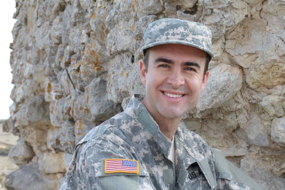 Man in military uniform smiles next to rocky outcropping.